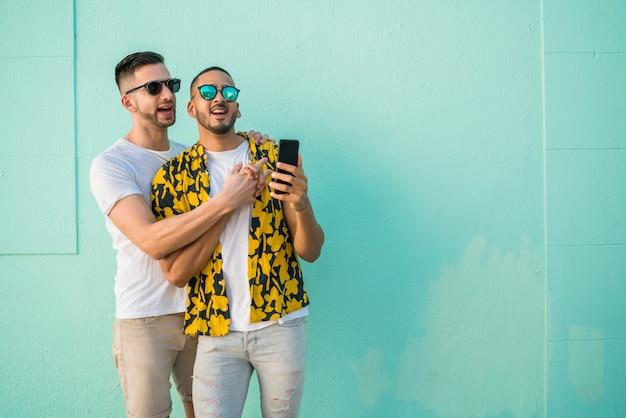 同性愛者のカップルが携帯電話でselfieを取ります。