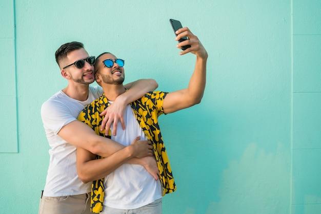 同性愛者のカップルが携帯電話でselfieを取る