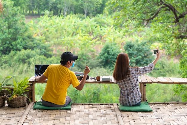 Азиатская женщина и человек в социальном дистанцировании сидя на стенде и принимают selfie посреди природы, социальной дистанцируя концепции.