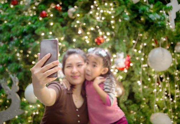 アジアの母の手がselfie写真を撮るために娘と一緒に携帯を保持する