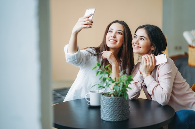 テーブルでselfieを取る携帯電話でカジュアルな若い屈託のないブルネットの女の子友達