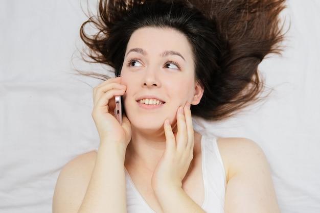 ベッドに横になっている女性が電話でselfieを作る