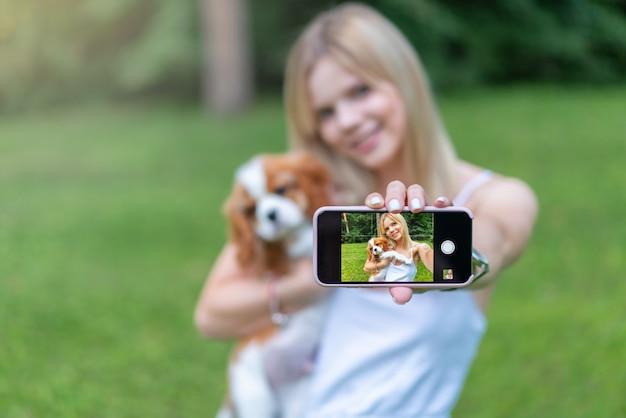 公園で美しい女性の肖像画、スパニエル犬とハグし、スマートフォンでselfieを作る