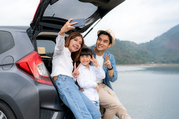 休暇で一緒に休暇中にスマートフォンで湖と山の景色と父、母と娘のselfieが付いている車に座っているアジアの家族の肖像画。幸せな家族の時間。