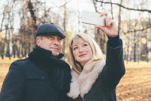 幸せな金髪熟女と美しい中年ブルネットは、携帯電話でselfieを取ります。