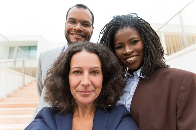 Счастливая успешная команда дела принимая selfie снаружи