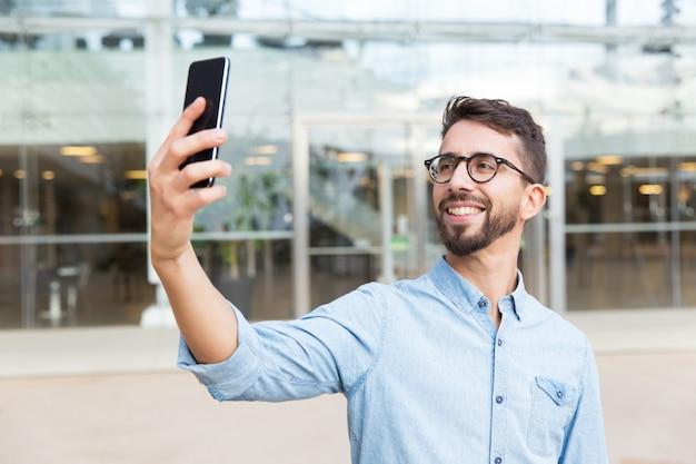 スマートフォンでselfieを取って眼鏡で幸せなうれしそうな男