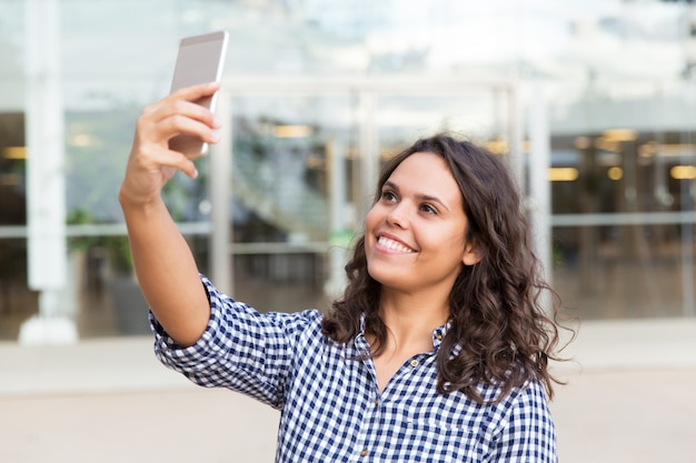 Selfieを取ってスマートフォンで幸せなうれしそうな女性