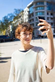 スマートフォンでselfieを取って美しい若い女性