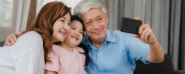 自宅で孫娘とアジアの祖父母selfie。シニア中国の幸せな家族の時間を過ごすには、リビングルームのソファーに横になっている若い女の子の子供と携帯電話を使用してリラックスします。
