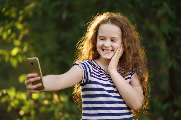 小さな巻き毛の少女は、屋外selfie写真を作ります。