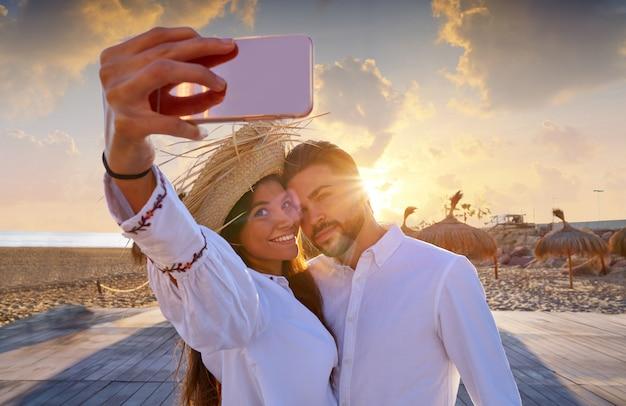 ビーチでの休暇のカップル若いselfie写真