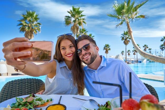 若いカップルselfieスマートフォンの写真