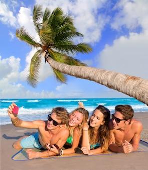 熱帯のビーチで観光客の友人のselfieグループ