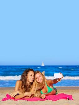 ビーチで横になっている幸せなガールフレンドselfieの肖像画