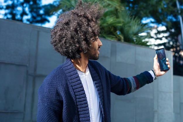 カジュアルな服装で携帯電話を使用して、街で屋外に立って、selfieをしながら笑顔のハンサムなアフロアメリカンの男の肖像