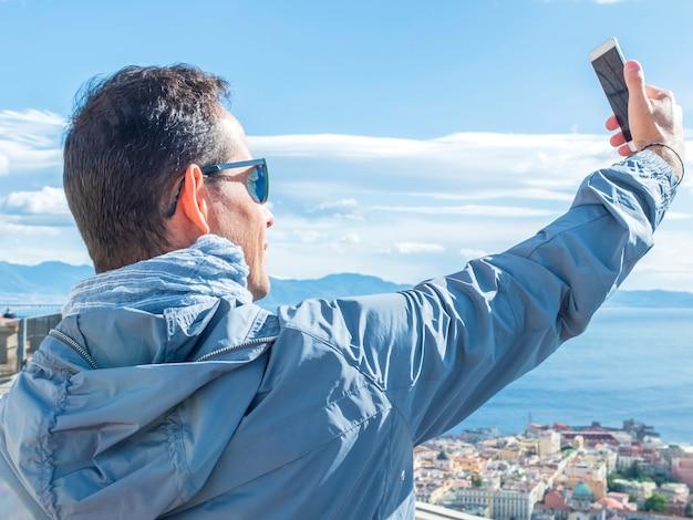 観光若い男selfieと彼はベルン市の旧市街でスマートフォンで写真を撮る