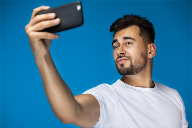 魅力的な男性は彼の携帯電話でselfieを作っています