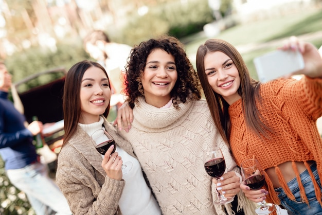若い女性は友達とピクニック中にselfieを作ります。