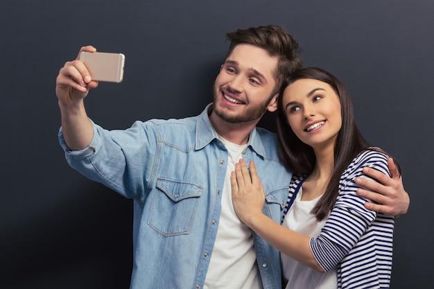カジュアルな服装の美しい若いカップルは、selfieを作っています。