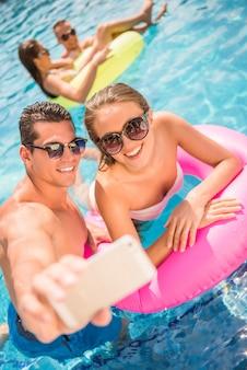 幸せなカップルはプールで楽しんでいる間selfieを作っています。