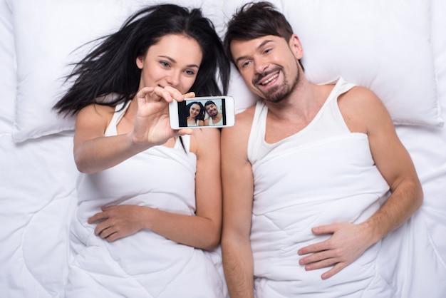 ベッドの中で幸せなカップルがselfieを作っています。