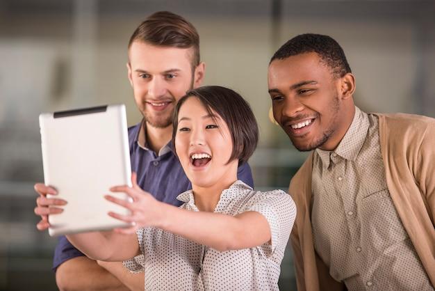 Selfieをやっているビジネス人々の若い笑顔グループ。