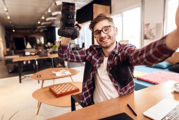 机に座ってラップトップでフリーランサー男撮影selfie。