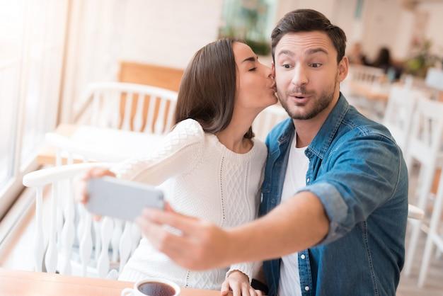 カップルがカフェでselfieをとります女性はキスをします。