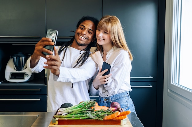 アフリカ系アメリカ人の少年と白い女の子が台所でselfieを作る