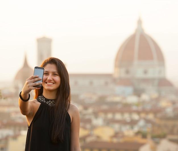 若いティーンはフィレンツェの日没でselfieを取ります