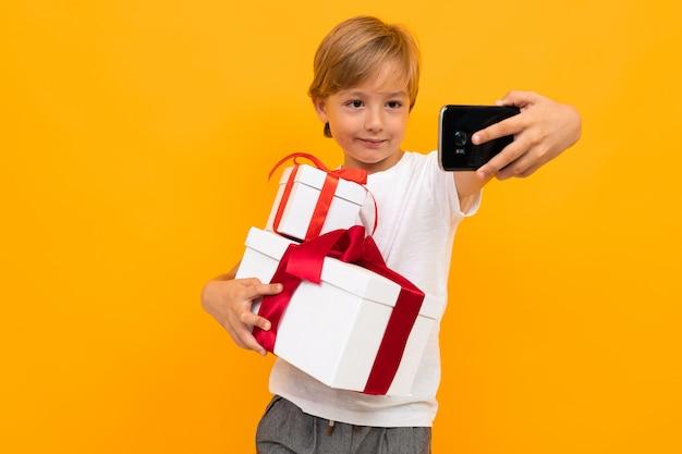 白人の少年はギフトと多くの白いボックスを保持し、selfie、黄色の壁に分離された肖像画