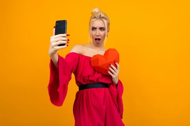 赤いドレスを着たセクシーな白人ブロンドの女の子は、オレンジのスタジオスペースで紙から赤いハートの電話でselfieを作る