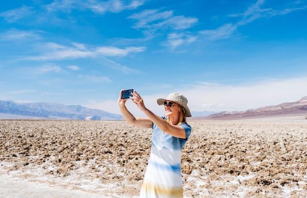 太陽の帽子と黄色と白の青い夏のドレスの美しい金髪の女性は、晴れた日にデスバレーの砂漠で携帯電話でselfie写真を撮る