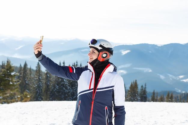Selfieを取って山でスキーの女の子