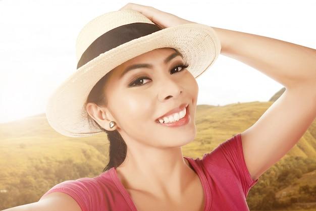 Азиатская женщина с соломенной шляпе, делая selfie с ее смартфон