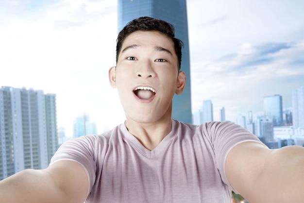 彼のスマートフォンでselfieを作るアジア人