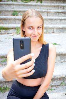 Selfieを取って黒の魅力的な若い女性。