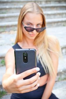 Selfieを取ってサングラスの魅力的な若い女性。