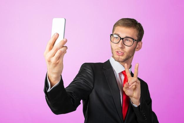 携帯電話でselfieを取ってハンサムな青年実業家