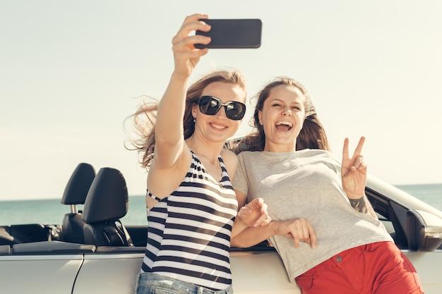 幸せな友達が車でselfieを引き継ぐ
