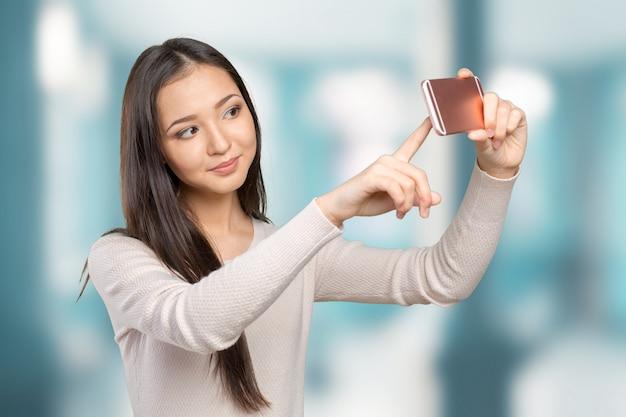 彼女のスマートフォンでselfieを作るうれしそうな若い女性