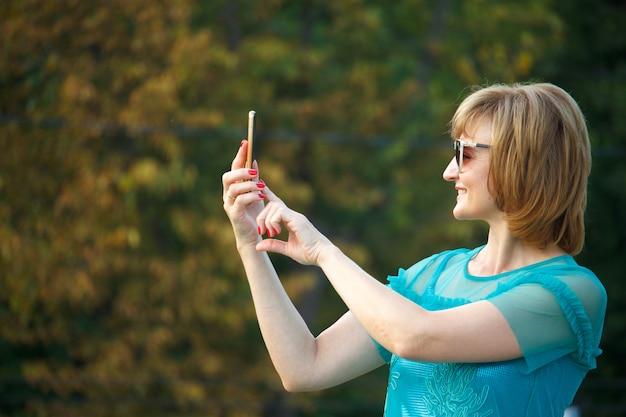 路上で大人の中年ビジネス女性は、スマートフォンでselfieを作ります。