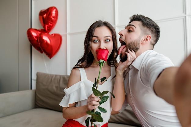 ハンサムなカップルの男と女のソファで自宅で赤いバラとハート形の風船でselfieを作る