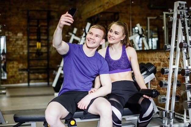 スポーツ服で美しい幸せなカップルは、スマートフォンを使用してselfieを作ると笑みを浮かべて
