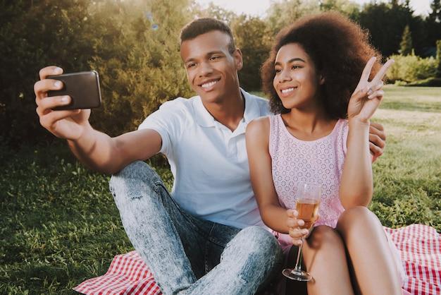 幸せな男と女は携帯電話でselfieをやっています。