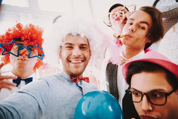 パーティーで電話でselfieを取って蝶ネクタイの同性愛者の人々。