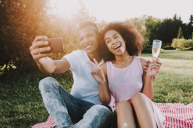 アフリカ系アメリカ人の人々は公園でselfieをやっています。