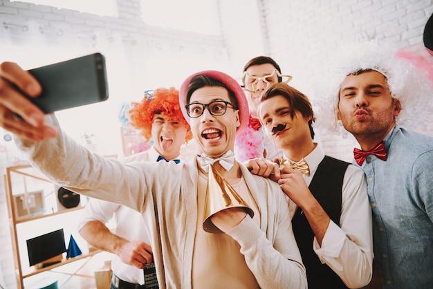 ゲイの男がパーティーで電話でselfieを取っています。