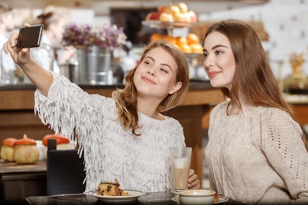 Правило селфи. снимок двух подруг, делающих селфи вместе за чашкой кофе, весело улыбаясь